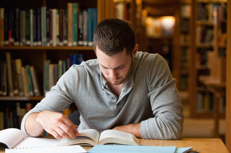 3650851-male-student-researching-with-a-book